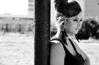 Гламурное фото девушки с перьевыми сережками, стоящей у столба