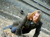 Динамичная фотография девушки на пленере с рельсами и шинами на заднем плане