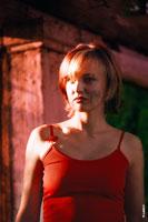 Летний фотопортрет девушки в красном в теплых тонах с солнечными бликами на лице