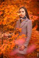 Осенний фотопортрет девушки в пальто, на красно-желтом фоне листвы