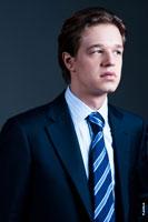 Деловой портрет мужчины в костюме с галстуком в студии на черном фоне. Поясной план