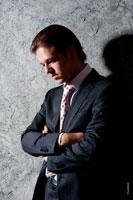 Фотопортрет делового задумчивого мужчины в костюме у стены, руки замкнуты на груди