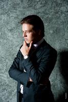 Бизнес-портрет делового мужчины с рукой у подбородка в профиль. Поясной портретный план