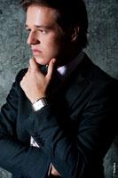 Деловой фото портрет мужчины в профиль с рукой у подбородка. Крупный план лица