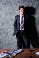 Модный мужской бизнес портрет для делового портфолио. Фото мужчины в студии у стены, перед столом, руки в карманах
