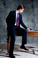 Фото делового мужчины в костюме, в полный рост, сидя на столе за ноутбуком