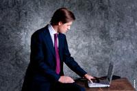 Бизнес-портрет делового мужчины в костюме, в профиль, сидя на столе за ноутбуком