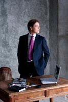 Фото делового мужчины в костюме перед столом в профиль