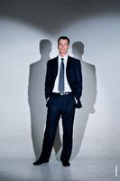 Деловой фото портрет мужчины в костюме в полный рост в студии, и две тени сзади