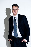 Поясной деловой фото портрет успешного делового человека в костюме, в очках, с жестким светом и с тенью на белом фоне