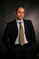 Студийный фотопортрет делового мужчины в костюме на темном фоне, с руками в карманах, по пояс
