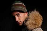 Горизонтальный студийный фотопортрет мужчины в полоборота в шапке и зимней куртке