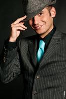 Позитивный фотопортрет телеведущего Андрея Разыграева с рукой у шляпы