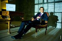 Модный студийный фотопортрет мужчины, сидя в кресле, в свете ночных городских огней