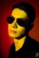 Модный фотопортрет мужчины в солнечных очках в черно-красно-желтых цветах