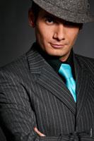 Фото Андрея Разыграева в костюме и шляпе, мужской фотопортрет с акцентом на взгляде. Крупный план лица
