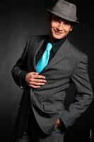 Еще одна портретная фотография Андрея Разыграева в костюме, бирюзовом галстуке и в шляпе с улыбкой настоящего шоумена