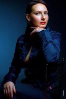 Женский студийный фотопортрет в синих тонах с рукой у лица
