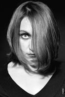 Женский фотопортрет в студии с модной прической: один глаз закрыт волосами