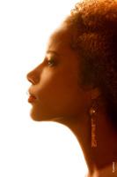Бьюти фото портрет девушки-мулатки в профиль на белом фоне