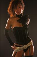 Студийный поясной фотопортрет девушки-мулатки в образе танцовщицы в темной тональности с боковыми бликами