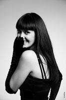 Актерский студийный фото портрет девушки, закрывающей улыбку рукой