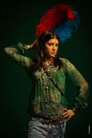 Фотопортрет девушки в студии с яркими перьями на голове