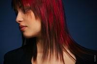 Рекламный фотопортрет девушки с яркой прической и красными прядями волос в темной тональности