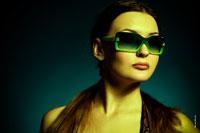 Горизонтальный модный фото портрет девушки в студии в солнечных очках
