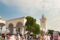 Общий вид железнодорожного вокзала Симферополя летом. Видны арки и вокзальная башня с часами