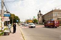 Мужик с тачкой и священник в черном идут по улице, справа видна часовня святителя Луки