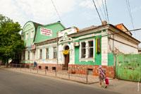 Старинный 1-этажный дом зеленого цвета с барельефом на фронтоне на улице Толстого в Симферополе