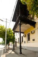 Фото большого чугунного балкона с кованными украшениями на фасаде дома Таврических губернаторов в Симферополе
