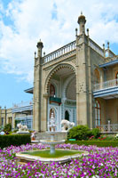 Фото клумбы с фонтаном на фоне южного фасада Алупкинского дворца в Крыму