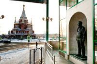 Фото памятника Михаилу Тимофеевичу Калашникову у его музея с видом на Михаило-Архангельский кафедральный собор в Ижевске