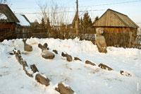 Фото заснеженной речки в музее-заповеднике «Лудорвай» со скульптурой рыбака и огромной рыбой