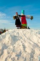 Фото ведущей праздника и чучела Масленицы на вершине снежного холма в «Лудорвае»