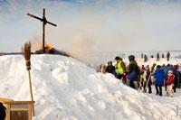 Кукла Масленицы сгорела. На вершине снежного холма догорает солома, и стоит черный крест