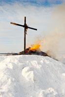 Фото черного креста в «Лудорвае» и догорающих частей чучела Масленицы на снежном холме
