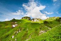 Синее небо, свет от солнца и тени от облаков на зеленых горных склонах