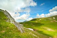 Горный фото пейзаж Лагонаки днем. На фото видны горные склоны, облака и синее небо