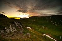 Горный фотопейзаж на закате. Видны горы и яркое закатное небо
