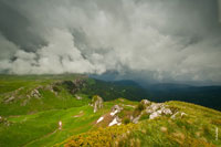 Грозовой горный фото пейзаж. Сильный ветер слева несет по склону, как по трамплину, густые облака