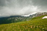Гора и предгорья Гузерипль стоят в темноте. Над ними висит плотный слой грозовых туч. Справа еще видно Оштен