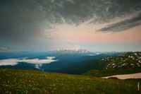 Горный фото пейзаж после заката. Сверху висят облака. В центре видно горы на фоне розового неба. Внизу — луга Лаго-Наки и низкие горы