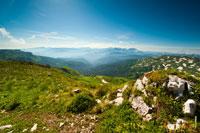 Красивый горный фотопейзаж: горные хребты вдали в воздушной перспективе, спереди камни