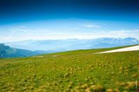В кадре синее небо, голубые воздушные перспективы гор вдали и луговые травы Лаго-Наки