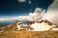 Красивый вид на один из скалистых гребней горы Оштен. Справа — густые белые облака на фоне синего неба