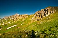 Горный фото пейзаж: травянистые горные склоны внизу, вверху справа скалистые гребни, слева видна гора Оштен