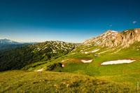 Пятнистая бело-зеленая гора Гузерипль, справа высится гора Оштен